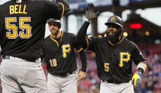 Pittsburgh Pirates' Josh Harrison (5) celebrates with Jordy Mercer (10) and Josh Bell (55) after hitting a three-run home run off Pittsburgh Pirates shortstop Alen Hanson in the fourth inning of a baseball game, Tuesday, May 2, 2017, in Cincinnati. (AP Photo/John Minchillo)