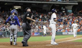Houston Astros' Marwin Gonzalez, right, watches his grand slam along with home plate umpire Pat Hoberg, center, and Texas Rangers catcher Jonathan Lucroy (25) during the eighth inning of a baseball game, Tuesday, May 2, 2017, in Houston. (AP Photo/David J. Phillip)