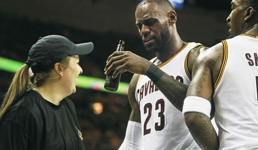 Cleveland Cavaliers forward LeBron James ends up with a beer bottle in his hand after running into a floor server while celebrating a victory against the Toronto Raptors during Game 1 of the second round playoff game, Monday, May 1, 2017 at Quicken Loans Arena in Cleveland. The Cavaliers defeated the Raptors 116-105. (Leah Klafczynski/Akron Beacon Journal via AP)