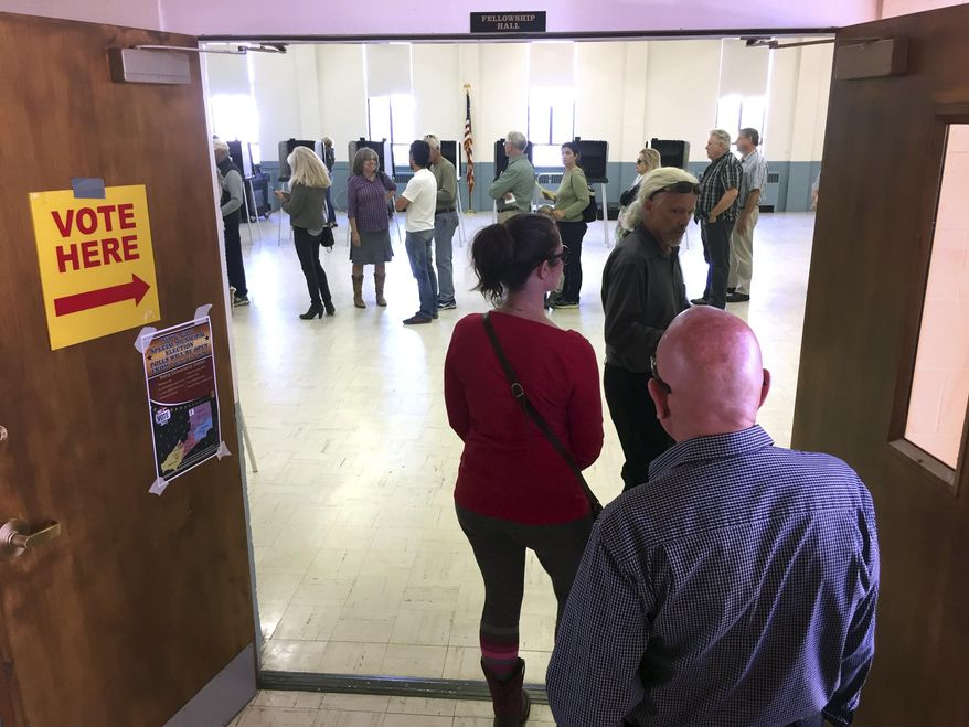 A line of more than 50 voters snakes though a balloting center in Santa Fe, N.M., on Tuesday, May 2, 2017, as voters decide whether to add a tax on sugary sodas and other sweetened beverages. The tax would follow the examples of several cities across the country. Under Santa Fe's approach, the tax would pay to expand early childhood education.(AP Photo/Morgan Lee)