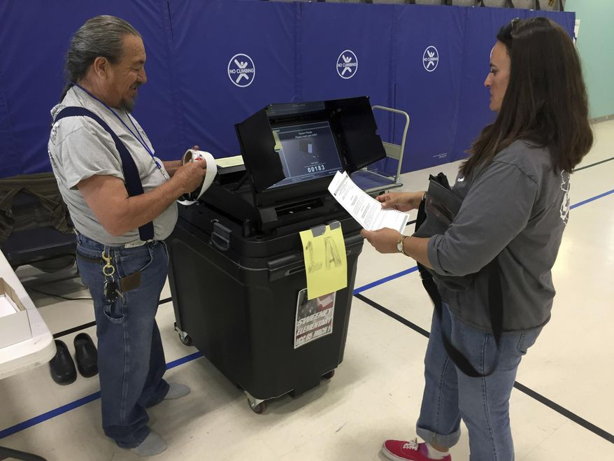 Middle school teacher Michelle Chavez, 48, of Santa Fe, N.M., right, casts her ballot with a poll worker at Sweeney Elementary School in Santa Fe, N.M., on Tuesday, May 2, 2017, in a citywide referendum. Voters in New Mexico's capital city were deciding whether to add a tax on sugary sodas and other sweetened beverages that would follow the examples of several cities across the country. The proposed tax in Santa Fe would pay to expand early childhood education. (AP Photo/Morgan Lee)