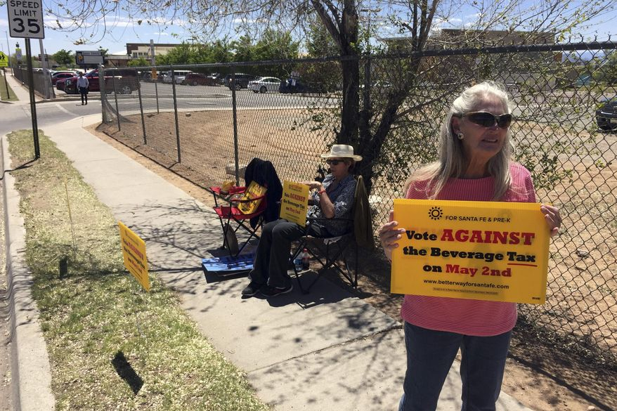 Coca-Cola Bottling Co. of Santa Fe Vice President Kathy Hart, 65, right, urges voters to reject a tax on sugary beverages outside a polling center in Santa Fe, N.M., on Tuesday, May 2, 2017. Voters in New Mexico's capital city were deciding whether to add a tax on sugary sodas and other sweetened beverages that would follow the examples of several cities across the country. The proposed tax in Santa Fe would pay to expand early childhood education. (AP Photo/Morgan Lee)