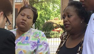 Katherine Thompson, left, daughter of Jammie Lane, and Youdella Allen, Lane's wife in 2009, talk with authorities after a news conference in Leesburg, Va., Tuesday, May 2, 2017, in which authorities announce that an alleged serial killer, Elias Abuelazam, confessed to the stabbing death of Lane eight years ago. (AP Photo/Matthew Barakat)