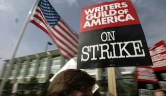 In this Nov. 9, 2007, file photo, Writers Guild of America (WGA) writers and others strike against the Alliance of Motion Picture and Television Producers (AMPTP) in a rally at Fox Plaza in Los Angeles' Century City district. (AP Photo/Reed Saxon, File) ** FILE **