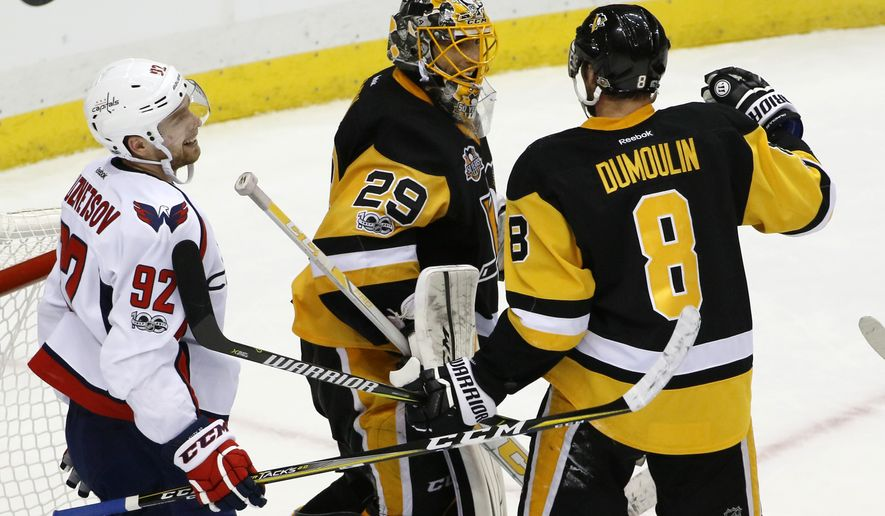 Pittsburgh Penguins goalie Marc-Andre Fleury (29) begins to celebrate with Alex Ovechkin (8) as Washington Capitals' Evgeny Kuznetsov (92) skates to the locker room following a 3-2 Penguins win in Game 4 of an NHL Stanley Cup Eastern Conference semifinal hockey game in Pittsburgh, Wednesday, May 3, 2017. (AP Photo/Gene J. Puskar)
