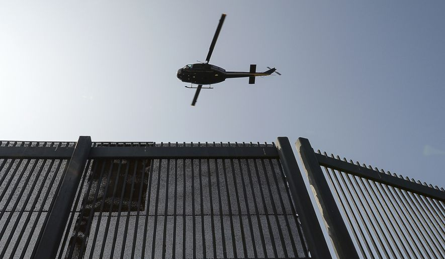 In this Tuesday, May 2, 2017, photo, a Customs and Border Protection helicopter flies at a low altitude over the U.S.-Mexico border fence near the Gateway International Bridge in Brownsville, Texas. (Jason Hoekema/The Brownsville Herald via AP)
