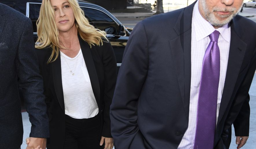 Singer Alanis Morissette, left, arrives with attorney Allen Grodsky at U.S. federal court for the sentencing in the embezzlement case of her former manager Jonathan Todd Schwartz, Wednesday, May 3, 2017, in Los Angeles. Schwartz pleaded guilty earlier this year after admitting he embezzled more than $7 million from the singer and other celebrities. (AP Photo/Chris Pizzello)