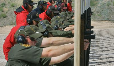 FILE - In this April 5, 2007 file photo, Border Patrol agent recruits practice small arms firing as senior agents, in red, watch at the Border Patrol Academy in Artesia, N.M. U.S. Customs and Border Protection, the parent agency of the Border Patrol and of Office of Field Operations, is taking steps to hire more agents and customs officers. President Donald Trump has ordered 5,000 new Border Patrol positions. (AP Photo/Matt York, File)