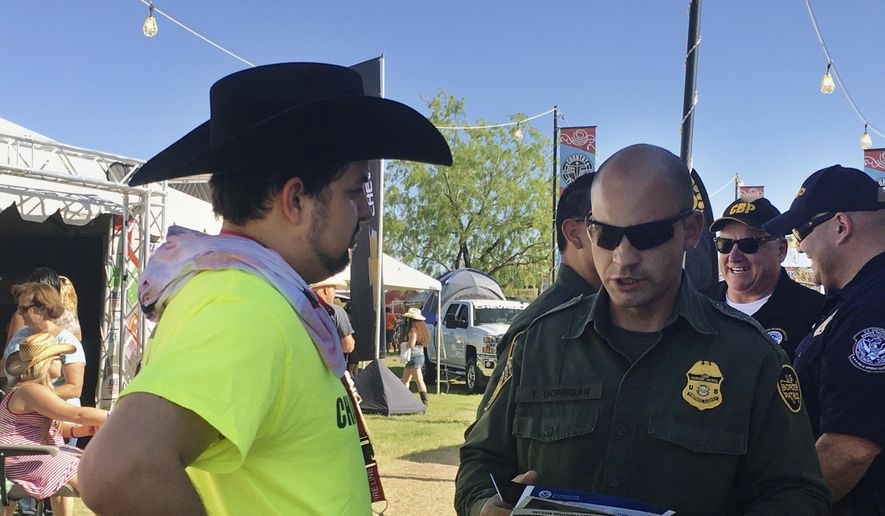 In this April 6, 2017, photo, a U.S. Border Patrol agent gives information about working for the agency to 24-year-old Ric Kindle, of the Phoenix area, at the Country Thunder Music Festival in Florence, Ariz. U.S. Customs and Border Protection, the parent agency of the Border Patrol and of Office of Field Operations, set up the recruitment booth at the festival in an effort to hire more agents and customs officers. (AP Photo/Astrid Galvan)