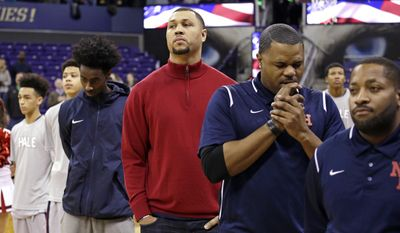 FILE - In this Feb. 8, 2017, file photo, Nathan Hale High School head coach and former NBA All-Star Brandon Roy, center, stands during the national anthem before a Metro League basketball game, in Seattle, Wash.  Authorities say former NBA player Brandon Roy was shot while attending a party in Southern California over the weekend. Los Angeles County sheriff's Lt. Joseph Williams said Wednesday, May 3, 2017, that Roy was one of four people shot in Compton on Saturday. (AP Photo/Elaine Thompson, file)