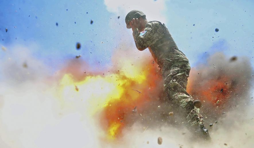 U.S Army combat camera photographer Spc. Hilda Clayton took this photo July 2, 2013 that was released by the U.S. Army, that shows an Afghan soldier engulfed in flame as a mortar tube explodes during an Afghan National Army live-fire training exercise in Laghman Province, Afghanistan. The accident killed Clayton and four Afghan National Army soldiers. (Spc. Hilda Clayton/U.S. Army via AP)
