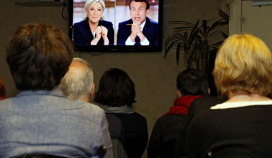 People watch a live broadcast television debate with French centrist presidential candidate Emmanuel Macron, right, and far-right candidate Marine Le Pen, Wednesday, May 3, 2017, in a bar of Biarritz, southwestern France.  Le Pen and Emmanuel Macron exchanged barbs and insults on Wednesday during their sole televised debate ahead of Sunday's runoff election. (AP Photo/Bob Edme)