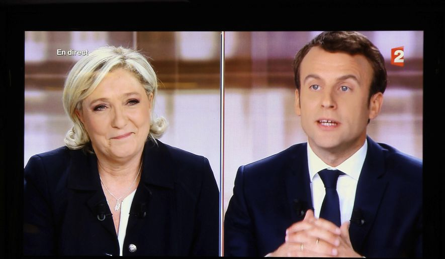 A television screen shows the live broadcast television debate with French centrist presidential candidate Emmanuel Macron, right, and far-right candidate Marine Le Pen, Wednesday, May 3, 2017, in a bar of Biarritz, southwestern France. French presidential candidates debate four days before the vote for the second round. (AP Photo/Bob Edme)