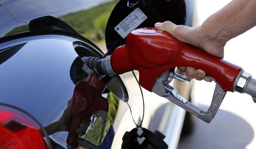 In this Thursday, July 16, 2015, file photo, a customer re-fuels her car at a Costco in Robinson Township, Pa. (AP Photo/Gene J. Puskar, File)