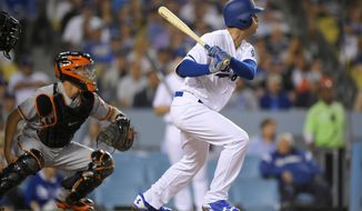 Los Angeles Dodgers' Cody Bellinger watches his three-run triple in front of San Francisco Giants catcher Nick Hundley during the second inning of a baseball game, Tuesday, May 2, 2017, in Los Angeles. (AP Photo/Mark J. Terrill)