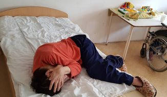 The April 18, 2017 photo provided by the Mental Disability Advocacy Center MDAC on Wednesday, May 3, 2017 shows a patient lies on his bed at an institution in the city of God, near Budapest, where some 220 people reside. MDAC said in a report Wednesday that it found signs of ill-treatment and malnutrition. (MDAC via AP)