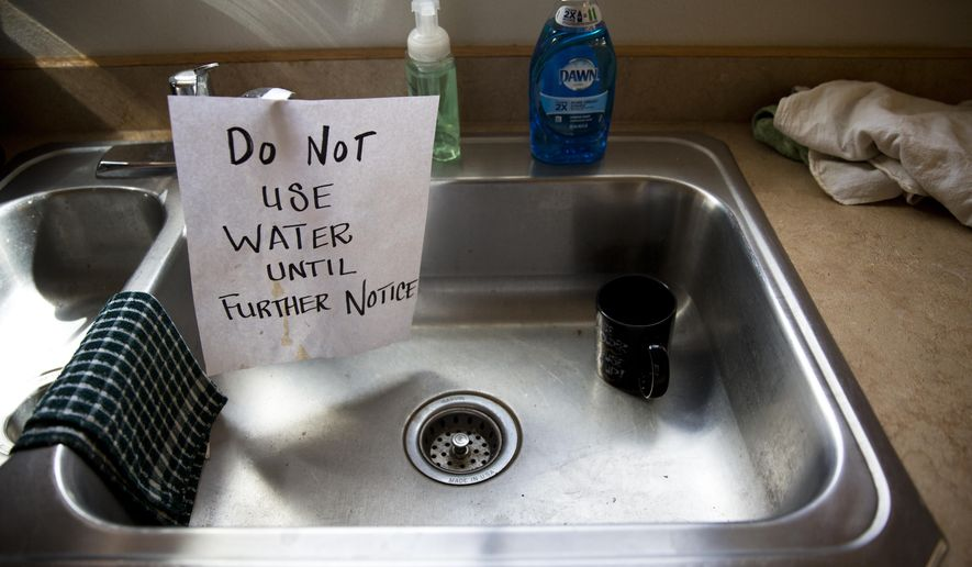In this April 5, 2017, photo, a sign warns people not to use contaminated water in a sink at Shoshone Fire Station No. 2 in Kellogg, Idaho. (Pat Sutphin/The Times-News via AP)