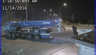 This photo obtained by The Associated Press shows security camera footage of a crane leaving Balad Air Base unchallenged by Sallyport Global security guards on Nov. 14, 2016, after it was involved in stealing generators. (Photo via AP)