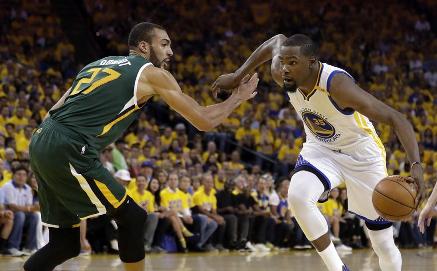Golden State Warriors' Kevin Durant (35) dribbles past Utah Jazz center Rudy Gobert (27) during the first half in Game 1 of an NBA basketball second-round playoff series, Tuesday, May 2, 2017, in Oakland, Calif. (AP Photo/Marcio Jose Sanchez)