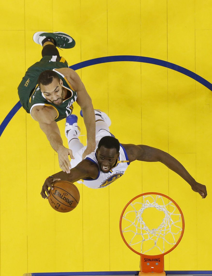 Golden State Warriors' Draymond Green, bottom, grabs a rebound next to Utah Jazz's Rudy Gobert during the first half in Game 1 of an NBA basketball second-round playoff series, Tuesday, May 2, 2017, in Oakland, Calif. (AP Photo/Marcio Jose Sanchez)