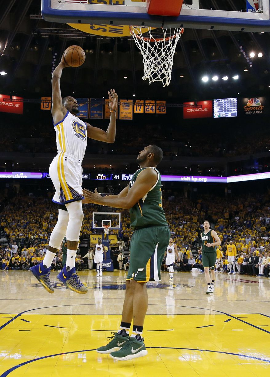 Golden State Warriors' Kevin Durant, left, dunks over Utah Jazz's Boris Diaw during the first half in Game 1 of an NBA basketball second-round playoff series, Tuesday, May 2, 2017, in Oakland, Calif. (AP Photo/Marcio Jose Sanchez)