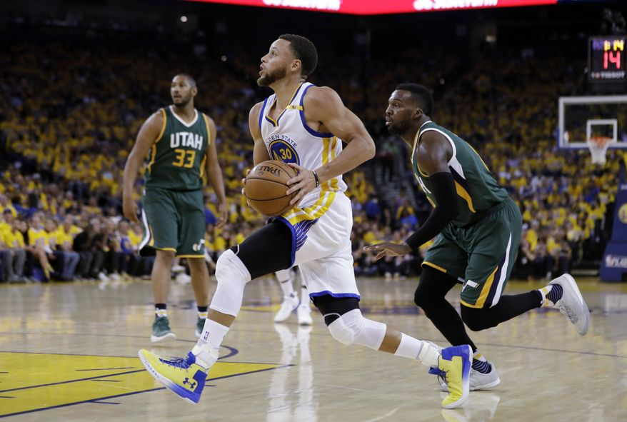 Golden State Warriors guard Stephen Curry, center, drives past Utah Jazz guard Shelvin Mack, right, during the first half in Game 1 of an NBA basketball second-round playoff series, Tuesday, May 2, 2017, in Oakland, Calif. (AP Photo/Marcio Jose Sanchez)