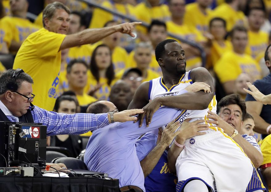 Golden State Warriors' Draymond Green falls onto fans after being fouled by Utah Jazz's Rudy Gobert, not seen, during the second half in Game 1 of an NBA basketball second-round playoff series, Tuesday, May 2, 2017, in Oakland, Calif. The Warriors won 106-94.(AP Photo/Marcio Jose Sanchez)