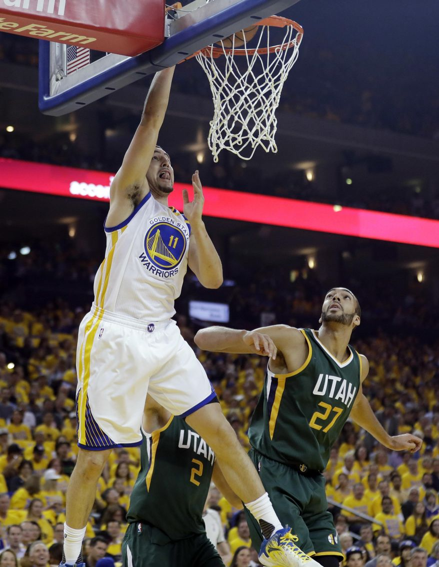 Golden State Warriors guard Klay Thompson (11) dunks past Utah Jazz center Rudy Gobert (27) during the first half in Game 1 of an NBA basketball second-round playoff series, Tuesday, May 2, 2017, in Oakland, Calif. (AP Photo/Marcio Jose Sanchez)