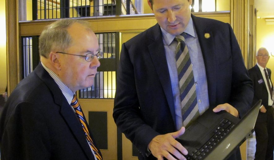 Kansas Senate Minority Leader Anthony Hensley, left, D-Topeka, confers with House Speaker Ron Ryckman Jr., right, R-Olathe, outside the Senate chamber, Wednesday, May 3, 2017, at the Statehouse in Topeka, Kan. Ryckman is showing Hensley figures related to a proposal for increasing income taxes to fix the state budget, trying to persuade Hensley that it also raises enough new revenue to boost aid to public schools. (AP Photo/John Hanna)