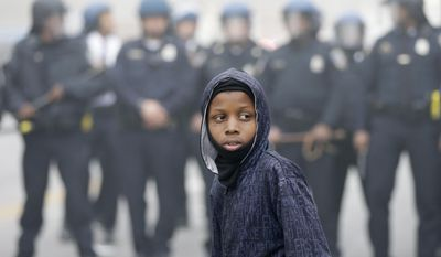 FILE - In this Monday, April 27, 2015 file photo, a boy stands in front of a police cordon following the funeral of Freddie Gray in Baltimore. The 25-year-old man was shackled but alive when he was put in Baltimore police van in April 2015. He came out with severe neck injuries, and his subsequent death led to rioting. Six officers were charged initially, but prosecutors in July dropped all remaining charges after acquittals and a hung jury. Gray's family agreed to a $6.4 million settlement with the city in September 2015. (AP Photo/Matt Rourke)