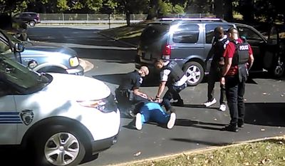 FILE - In this Tuesday, Sept. 20, 2016 image taken from video recorded by Keith Lamont Scott's wife, Rakeyia Scott, Charlotte police gather next to Keith Lamont Scott as Scott lies face-down on the ground in Charlotte, N.C. In the video of the deadly encounter between Charlotte police and the black man, Rakeyia Scott repeatedly tells officers her husband is not armed and pleads with them not to shoot him as they shout at him to drop a gun. The video does not show clearly whether Scott had a gun. (Rakeyia Scott/Curry Law Firm via AP)