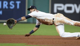 Houston Astros first baseman Marwin Gonzalez dives for but can't reach a ball hit for a single by Texas Rangers' Rougned Odor during the sixth inning of a baseball game Wednesday May 3, 2017, in Houston. (AP Photo/George Bridges)