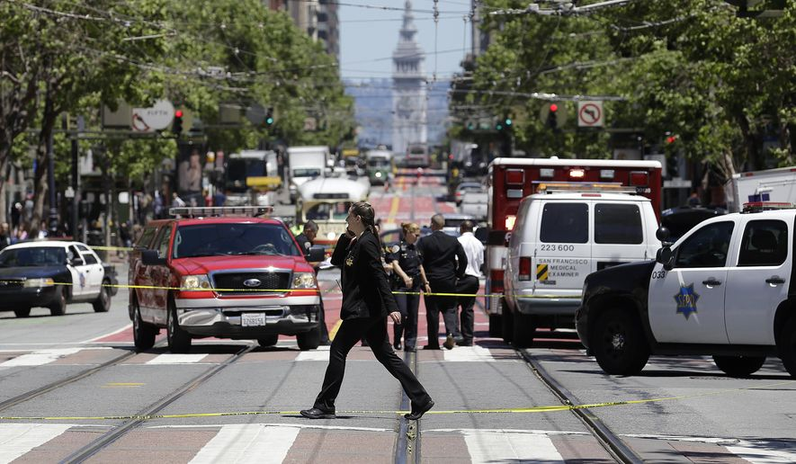 Police officers and officials patrol along Market Street after a shooting in San Francisco, Wednesday, May 3, 2017. (AP Photo/Jeff Chiu)