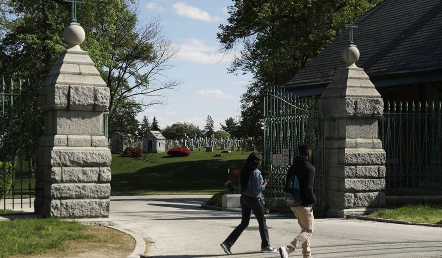 People walk past a gate to Holy Cross Cemetery, Wednesday, May 3, 2017, in Yeadon, Pa. The body of 19th century serial killer Dr. H. H. Holmes is being exhumed from the cemetery in suburban Philadelphia at the request of his great-grandchildren, who hope identifying his remains will quell centuries-old rumors that he conned his way out of his execution and escaped from prison. (AP Photo/Matt Slocum)