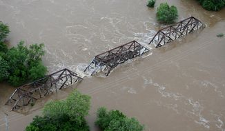 In this Tuesday, May 2, 2017 photo, flood water from the Meramec River streams over a railroad bridge in Valley Park, Mo. River levels are cresting in several Missouri communities as floodwaters slowly drain from the state, although forecasts for more rain could cause another round of damaging high water. (David Carson/St. Louis Post-Dispatch via AP)