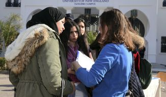 In this Feb. 18, 2017 photo provided by the University of New England, political science major and resident assistant Clancy Phillips, right, speaks to prospective students at an open house on the school's satellite campus in the Moroccan coastal city of Tangier. In response to concerns about anti-immigrant sentiment, some U.S. colleges are making new efforts to help international students feel welcome and reassure them of their safety. (Rachid Ouettassi/University of New England via AP)