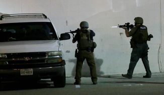 Police check a car early Friday, July 8, 2016, in Dallas, Snipers opened fire on police officers in Dallas on Thursday night; some of the officers were killed, police said. (AP Photo/LM Otero)