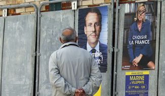 A man walks past defaced election campaign posters for French centrist presidential candidate Emmanuel Macron and far-right candidate Marine Le Pen, in Saint Jean de Luz, southwestern France, Thursday, May 4, 2017. France will vote on Sunday May 7 in the second round of the presidential election. (AP Photo/Bob Edme)