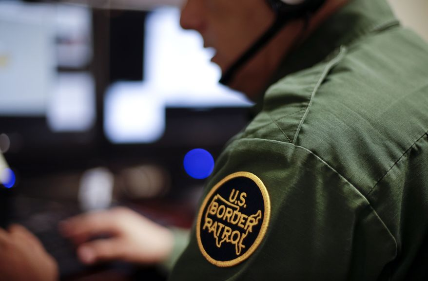 In this June 5, 2014, file photo, a Border Patrol agent uses a headset and computer to conduct a long-distance interview by video from a facility in San Diego. (AP Photo/Gregory Bull, File)
