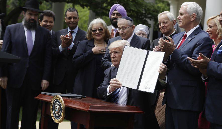 President Donald Trump holds a signed executive order aimed at easing an IRS rule limiting political activity for churches, Thursday, May 4, 2017, in the Rose Garden of the White House in Washington.  (AP Photo/Evan Vucci)