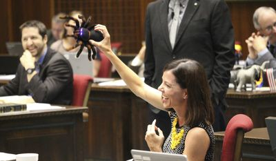 In a light-hearted moment during tense budget debate in the Arizona Legislature, Republican Rep. Michelle Ugenti-Rita holds up a plastic tarantula in Phoenix, Ariz., Thursday, May 4, 2017. Ugenti-Rita had just screamed in fright when she spotted it under her desk. The Arizona Legislature was moving closer to passing a state budget plan late Thursday afternoon, with deal-cutting securing support from defiant Republicans in an effort to gain passage without minority Democratic support. (AP Photo/ Bob Christie)