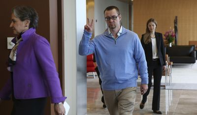Following attorney Terri Mascherin, left, Adam Gray gives the peace sign as he enters the room for a press conference Thursday, May 4, 2017. Gray who was sent to prison after barely turning 14, was released from an Illinois prison Wednesday after Cook County prosecutors recently decided to dismiss the charges against him. They said fire science advancements raised too many questions about his conviction. (Nancy Stone//Chicago Tribune via AP)