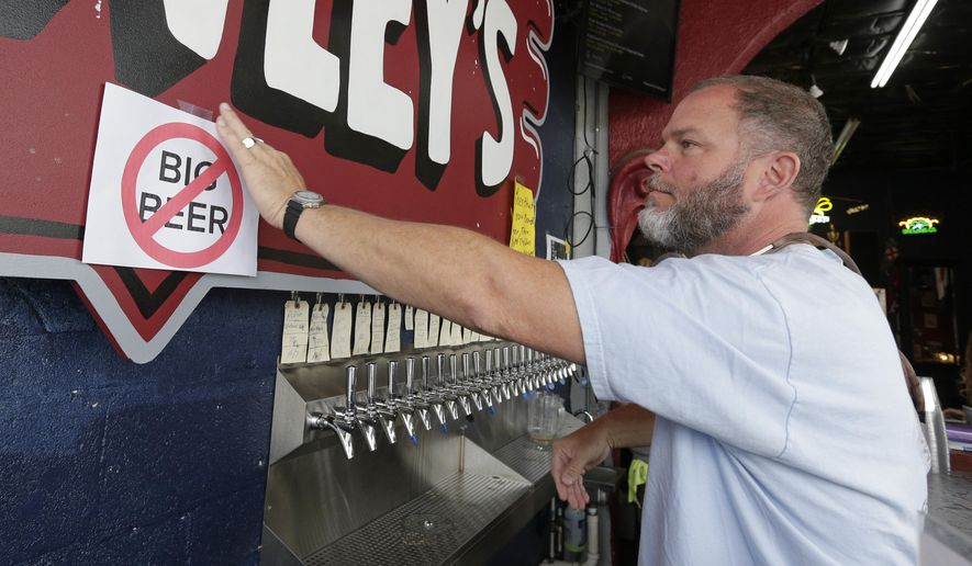 "Michael Brawley places a ""No Big Beer"" sign behind the bar at Brawley's Beverage in Charlotte, N.C., Thursday, May 4, 2017. Brawley is among at least a handful of stores or restaurants that announced they don't intend to stock Wicked Weed in the future.(AP Photo/Chuck Burton)"