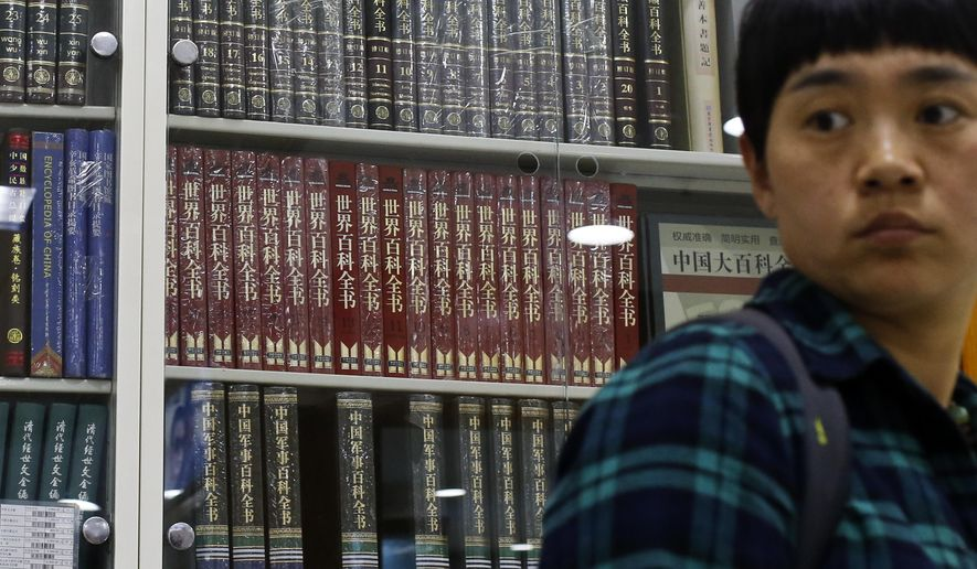 A woman walks by a cabinets displaying Chinese version of foreign and local encyclopedias at a book store in Beijing, Thursday, May 4, 2017. China is compiling a free online encyclopedia to rival Wikipedia, but it will likely only give Beijing's official version of sensitive historical events, and the public won't be able to write or edit it. (AP Photo/Andy Wong)