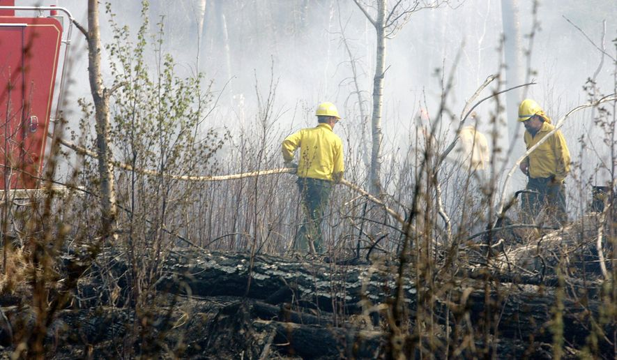 ADVANCE FOR USE SATURDAY, MAY 6 AND THEREAFTER - In this May 12, 2017, file photo, firefighters battle fire along the Gunflint Trail north of Grand Marais, Minn. as they continue the fight against the week-old fire that has destroyed over 50,000 acres and over 100 structures. The fire began May 5, 2007, with a seemingly innocent campfire. It quickly blew out of control, fanned by erratic winds and fueled by tinder dry conditions. It took 1,000 firefighters from around the country a week to finally corral it. (AP Photo/Jim Mone, File)