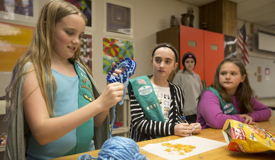 ADVANCE FOR THE WEEKEND OF FEB. 1 - In this Tuesday, Jan. 26, 2016 photo, Girl Scout Troop 6111 member Julia Caldwell, 10, from left, shows off the scarf she is making for the  Evergreen Community Initiative to other members Ella Bancker, 11, and, Ellie Weisbrot, 10, at Plover-Whiting Elementary School in Stevens Point, Wis. The community initiative gives scarves away to those in need. The scarves are currently hanging on trees by the Portage County Library. (Megan McCormick/The Stevens Point Journal via AP) MANDATORY CREDIT