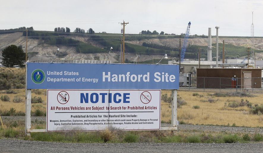 FILE - In this July 9, 2014, file photo, a sign informs visitors of prohibited items on the Hanford Nuclear Reservation near Richland, Wash. A new report says Congress should consider authorizing the Department of Energy to use grout to stabilize some of Hanford's radioactive waste, rather than a more expensive plan to turn it into glass. (AP Photo/Ted S. Warren, File)
