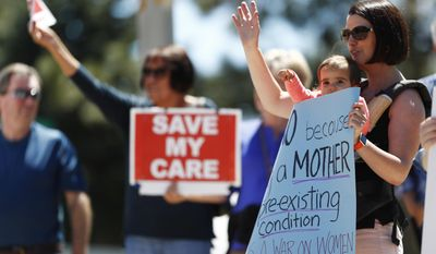 Cindy Fandhu, front right, holds her 18-month-old daughter, Jocelyn, as they wave to supporters during a protest outside the office of U.S. Rep. Mike Coffman, R-Colo., over the health care overhaul bill up for a vote in the U.S. House Thursday, May 4, 2017, in Aurora, Colo. (AP Photo/David Zalubowski)