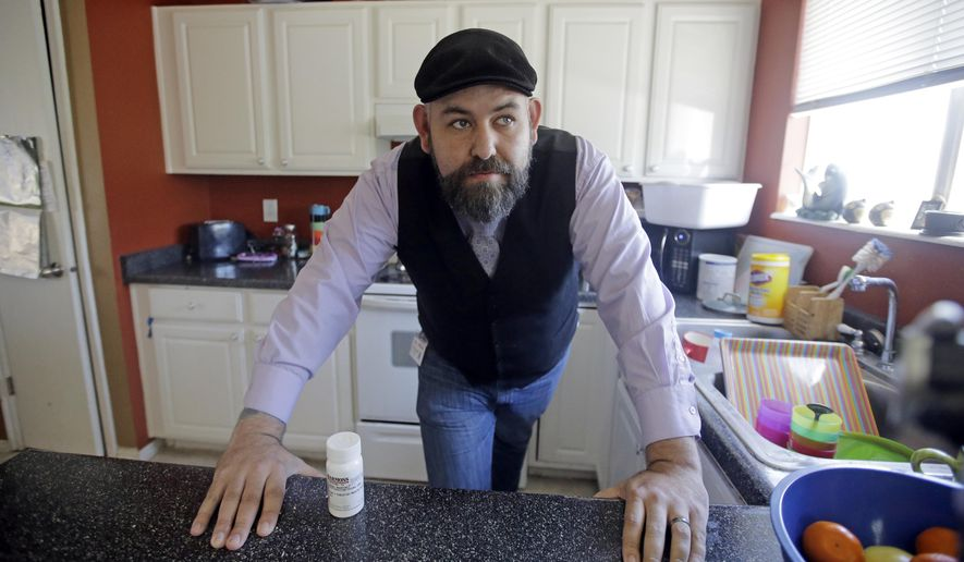 Jake Martinez, 32, looks on as he stands next to his medication at his home Thursday, May 4, 2017, in Murray, Utah. Martinez, who has epilepsy, is worried about health insurance as Republicans move closer to dismantling the Obama health care system, known as the Affordable Care Act, which he and his wife use. (AP Photo/Rick Bowmer)
