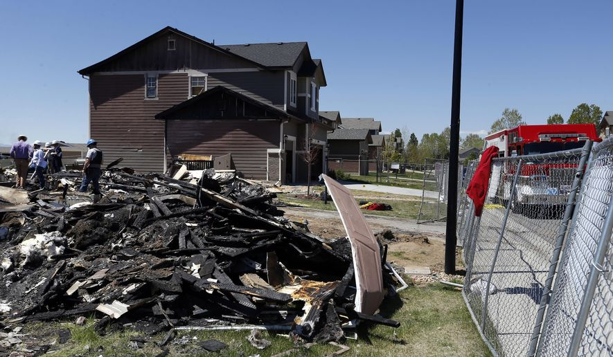 Workers dismantle the charred remains of a home at the location where an unrefined petroleum industry gas line leak explosion killed two people inside their home, in Firestone, Colo., Thursday, May 4, 2017. Fire officials said that an investigation has revealed that the April 17, 2017 explosion was caused by unrefined natural gas that was leaking from a small abandoned pipeline from a nearby well owned by Anadarko Petroleum. (AP Photo/Brennan Linsley)